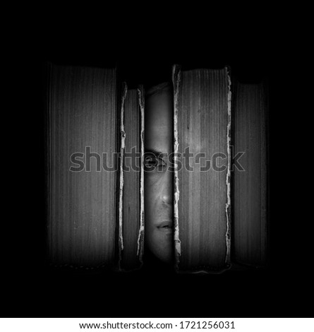 Surreal scene with close-up man's face with an amazed expression between old books on dark background. Bibliophile, education importance and imaginative literature concept. Black and white photography