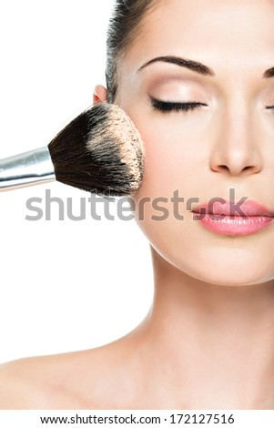 Closeup portrait of a woman  applying dry cosmetic tonal foundation  on the face using makeup brush.  #172127516