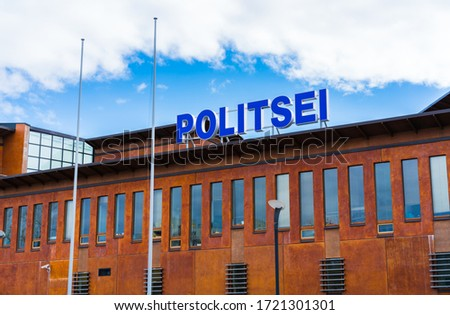 "Tallinn City Centre Police Station on Kolde street. Big sign ""Police"" on top of the brown / orange building. Empty flag poles in front of the office. New modern police station building. Sunny sky"