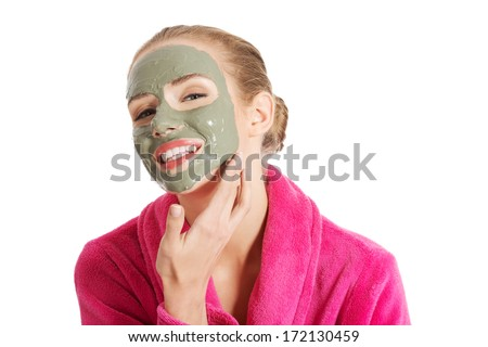 Beautiful woman in pink bathrobe and havinf facial mask. Isolated on white. #172130459