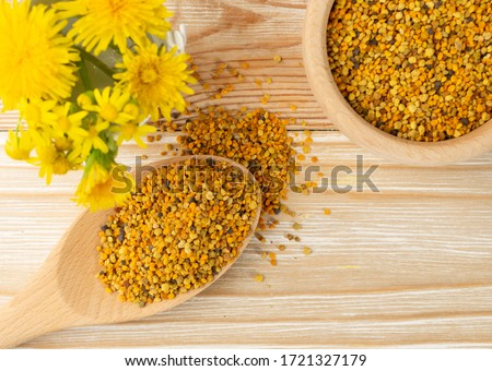 Macro shot of bee pollen or perga in wooden spoon on blurred rustic background. Raw brown, yellow, orange and blue flower pollen grains or bee bread. Healthy food supplement with selective focus Royalty-Free Stock Photo #1721327179