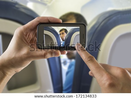 Passenger photographing a cellphone to a surprised passengers inside an airplane