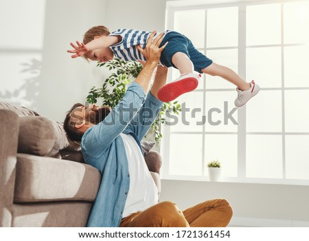 Joyful young man in casual wear sitting on floor and throws up happy little son while having fun together in cozy living room at home