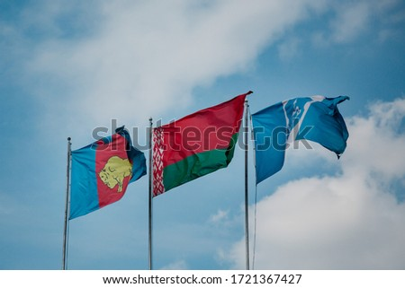 Three flags fly in the wind (from left to right): flag of Brest region, flag of Belarus, flag of Brest. Picture made during coronavirus pandemic in the world.
