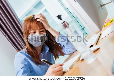 Asian young business woman wearing face mask protective working from home office with laptop computer he quarantines disease coronavirus or COVID-19 and write note booklist work today #1721372926