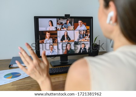 Morning meeting online. A young woman is using app on pc for connection with colleagues, employees. Video call with many people together. Back view Royalty-Free Stock Photo #1721381962