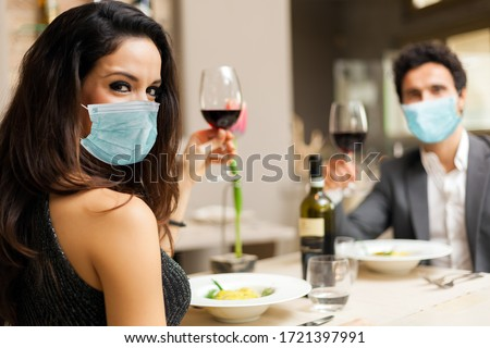 Couple toasting wineglasses in a luxury restaurant and wearing masks, coronavirus concept #1721397991