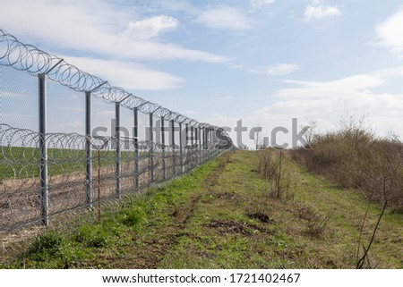 Border fence between Rastina (Serbia) & Bacsszentgyorgy (Hungary). This border wall was built in 2015 to stop the incoming refugees & migrants during the refugees crisis, on Balkans Route.   #1721402467