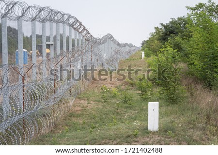 Border fence between Subotica (Serbia) & Kelebia (Hungary) with boundary marker. This border wall was built to stop the incoming refugees & migrants during the refugees crisis, on Balkans Route.   Royalty-Free Stock Photo #1721402488