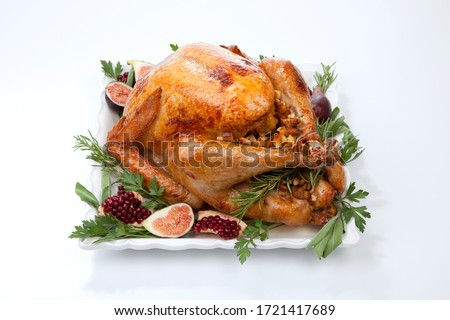 Garnished traditional roasted turkey, garnished with fresh figs, pomegranate, and herbs. On white background. #1721417689