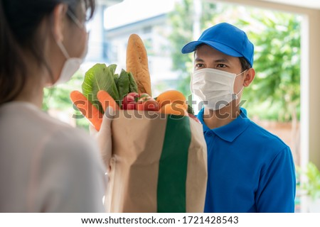 Asian delivery man wearing face mask and glove with groceries bag of food, fruit, vegetable give to woman costumer in front of the house during time of home isolation. #1721428543