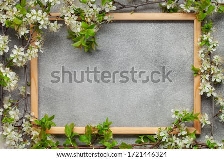 Blossom branch of cherries on a picture frame on a grey background. Top view. Copy space