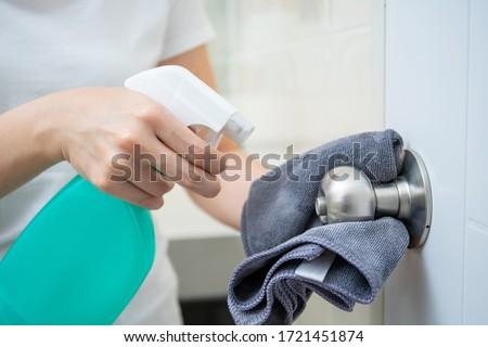 Woman house keeper cleaning a dirty stainless door knob in toilet. Maid spraying liquid cleaning solution on the dirty door knob handle in toilet and using micro fabric wipe on door knob surface. #1721451874