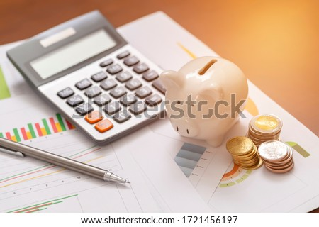 Piggy bank and coins for saving money with business stuff, Business and finance concept, Royalty-Free Stock Photo #1721456197