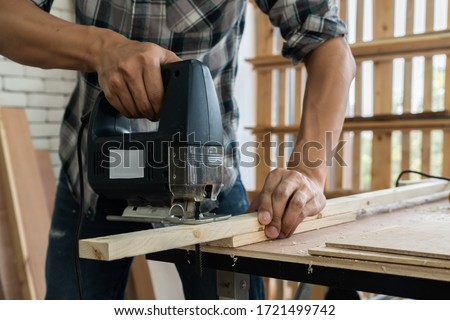 Carpenter working on wood craft at workshop to produce construction material or wooden furniture. The young Asian carpenter use professional tools for crafting. DIY maker and carpentry work concept. #1721499742