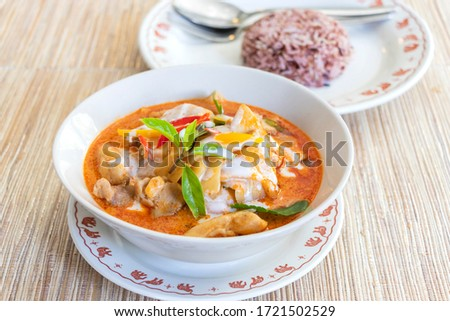 image of chicken with red curry and bamboo shoots vegetable topping with red chili, basil leaves and coconut cream, served with red rice for healthy.    #1721502529
