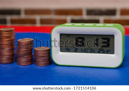 A stack of Nigerian coins placed next to a green alarm clock resting on a blue floor with brick background. Concept of using time to run and grow  business. Pic taken in Port Harcourt  Nigeria 2020.