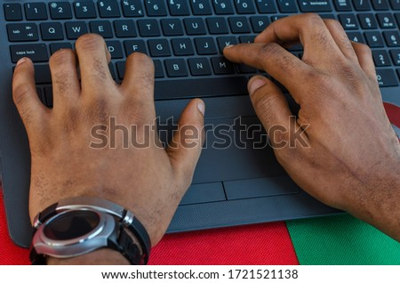 A Nigerian business man is typing on keyboard of laptop checking electronic mail, preparation of presentation in meeting, shopping online. Pic taken in Port Harcourt Nigeria 2020