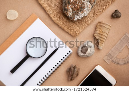 Stone samples, loop, notebook and mobile phome at geological laboratory. Geology rock laboratory. Laboratory for analysis of geological soil materials, stones, minerals, rocks samples for researchers Royalty-Free Stock Photo #1721524594