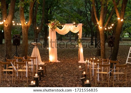 Wedding arch in the woods with light bulbs. Beautiful wedding rustic in the forest. Seats for guests at a beautiful wedding with light bulbs in the forest. #1721556835