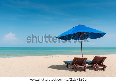 Wooden beach bench under parasol umbrella on tropical island beach. Holiday relaxation with turquoise sea and blue sky landscape. Summer vacation travel concept Royalty-Free Stock Photo #1721591260
