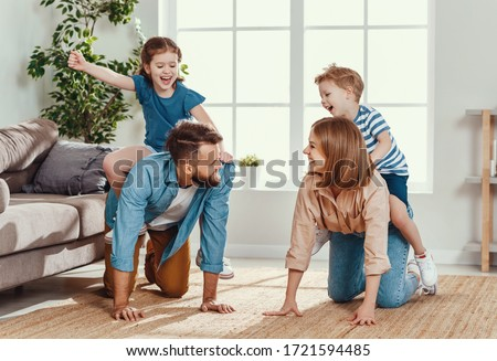 Cheerful young couple laughing   while having fun and giving piggyback ride to happy active kids in cozy living room