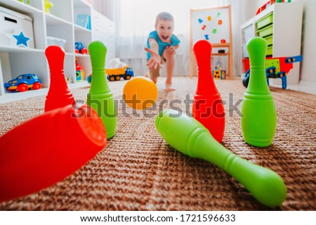 children a boy throws ball into a home bowling alley and smashes the bowling pins. Selective focus. concept of active play in the home room, quarantine, self-isolation, achieving goal
