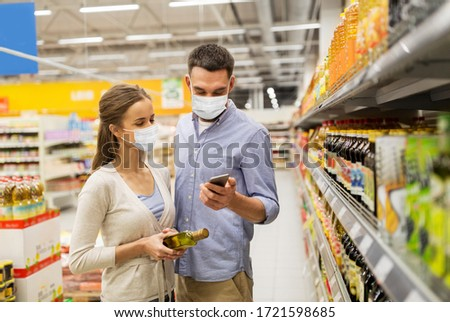 food shopping, consumerism and pandemic concept - happy couple wearing face protective medical masks for protection from virus disease with smartphone buying olive oil at grocery store or supermarket #1721598685