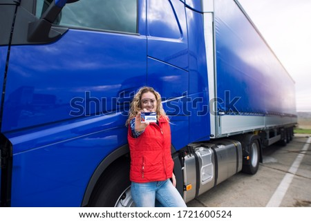 Truck driver showing commercial driving license. CDL training. #1721600524