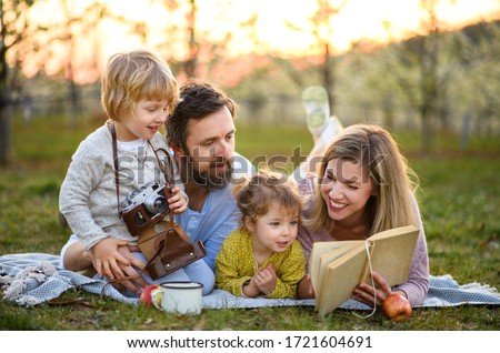 Family and small children with camera and book outdoors in spring nature, resting. #1721604691