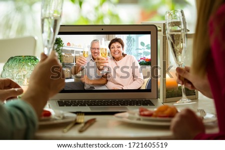 Man and woman sitting at the dining table, having dinner, drinking Champagne and having video call with senior parents on laptop. Staying home, quarantine and social distancing celebration of event.  #1721605519