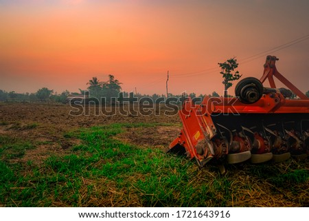 Ridging crackdown machine. Supply for tractor. Agricultural machinery in agriculture farm. Rice farm in morning with red sunrise sky. Nature of farmland. Farmer hut and electric pole in farmland. #1721643916