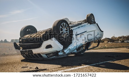Horrific Traffic Accident, Rollover Smoking and Burning Vehicle Lying on its Roof in the Middle of the Road after Collision. Daytime Crash Scene with Severely Damaged Car. Royalty-Free Stock Photo #1721657422