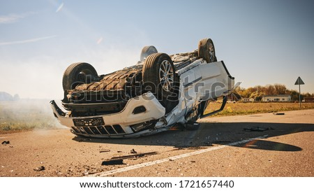 Horrific Traffic Accident, Rollover Smoking and Burning Vehicle Lying on its Roof in the Middle of the Road after Collision. Daytime Crash Scene with Severely Damaged Car. Royalty-Free Stock Photo #1721657440