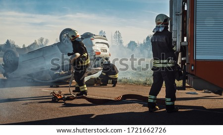 Rescue Team of Firefighters Arrive at the Crash, Catastrophe, Fire Site on their Fire Engine. Firemen Grab their Equipment, Prepare Fire Hoses and Gear from Fire Truck, Rush to Help Injured People. Royalty-Free Stock Photo #1721662726