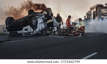 Car Crash Traffic Accident: Paramedics and Firefighters Rescue Injured Trapped Victims. Medics give First Aid to a Female Passenger. Firemen Use Hydraulic Cutters Spreader to Open Vehicle Royalty-Free Stock Photo #1721662744