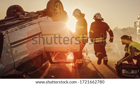 Car Crash Traffic Accident: Paramedics and Firefighters Plan Rescuing Passengers Trapped in Rollover Vehicle. Medics Prepare Stretchers and First Aid Equipment. Firemen Use Hydraulic Cutters Spreader Royalty-Free Stock Photo #1721662780