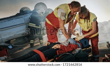 On the Car Crash Traffic Accident Scene: Paramedics Saving Life of a Female Victim who is Lying on Stretchers. They Apply Oxygen Mask, Do Cardiopulmonary Resuscitation / CPR and Perform First Aid #1721662816