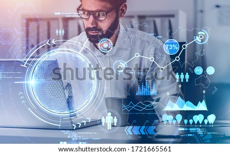 Serious bearded young businessman in glasses using laptop in blurry room with double exposure of immersive online business interface. Toned image. Elements of this image furnished by NASA