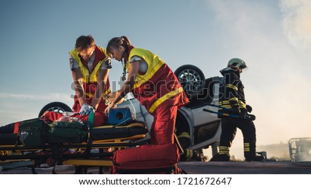 On the Car Crash Traffic Accident Scene: Paramedics Saving Life of a Female Victim who is Lying on Stretchers. They Apply Oxygen Mask, Do Cardiopulmonary Resuscitation / CPR and Perform First Aid #1721672647