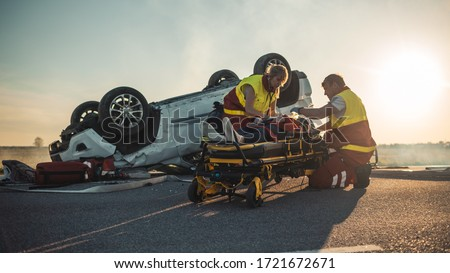 On the Car Crash Traffic Accident Scene: Paramedics Saving Life of a Female Victim who is Lying on Stretchers. They Listen To a Heartbeat, Apply Oxygen Mask and Give First Aid. Background Firefighters Royalty-Free Stock Photo #1721672671
