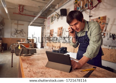 Male Business Owner In Workshop Using Digital Tablet And Making Call On Mobile Phone Royalty-Free Stock Photo #1721678116