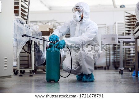 Man in protective suit and mask disinfecting warehouse full of food products from corona virus / covid-19. #1721678791