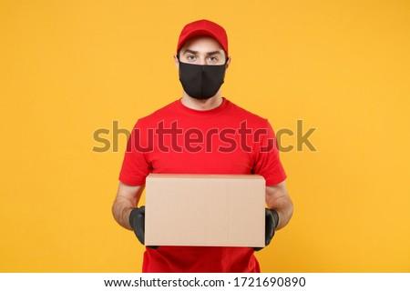 Delivery man employee in red cap blank tshirt uniform face mask glove hold empty cardboard box isolated on yellow background studio Service quarantine pandemic coronavirus flu virus 2019-ncov concept #1721690890