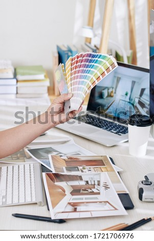 Interior designer choosing color palette for new project and looking at printed photos of rooms