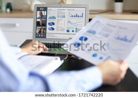 Business woman talking to her colleagues in video conference. Multiethnic business team working from home using laptop, discussing financial report of their company. Royalty-Free Stock Photo #1721742220