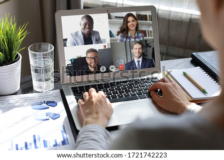 Business woman talking to her colleagues in video conference. Multiethnic business team working from home using laptop. #1721742223