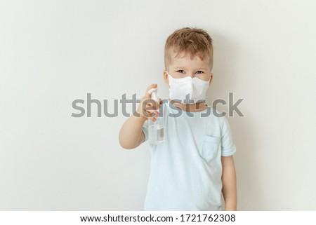 Boy in Medical Face Mask Hold Sanitiser Bottle. Caucasian Child Wearing Flu Protection Looking at Camera. Toddler Showing Antiseptic, Sterilization Gel. Corona Virus Pandemic Concept #1721762308