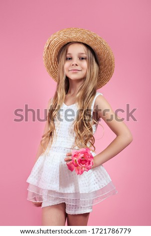 Stylish kid girl in straw hat and white dress posing over pink background