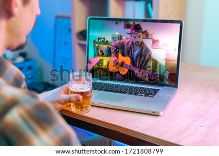 Coronavirus. Back view of man watching live video concert while staying at home. Close up of a man enjoying musical concert on laptop. Stay at home. Quarantine. Isolated. #1721808799